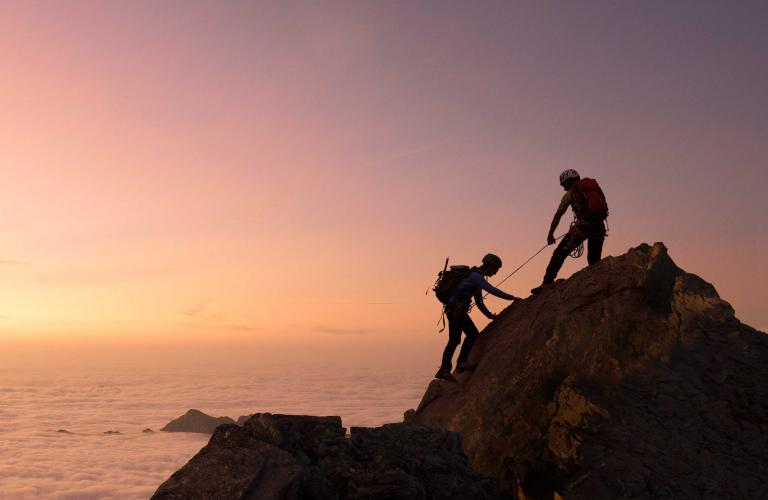 Image of two mountain climbers and a sunset.