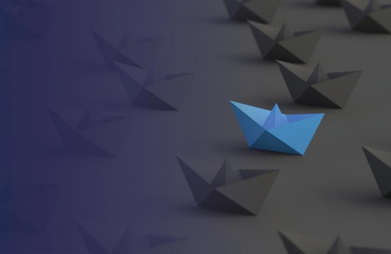 Blue paper boat among black paper boats